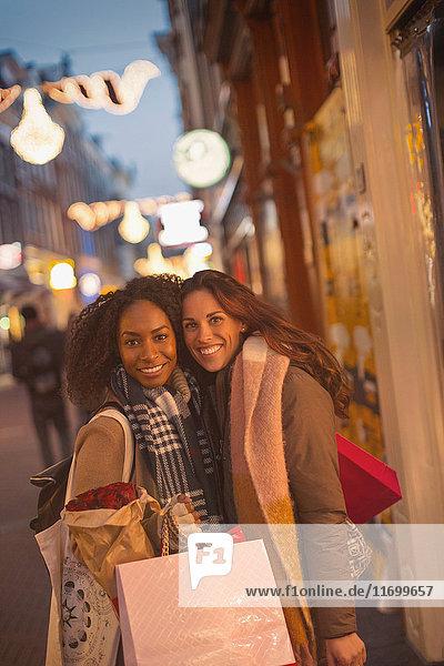 Portrait lächelnde junge Frauen Freunde mit Einkaufstaschen auf urbaner Nachtstraße