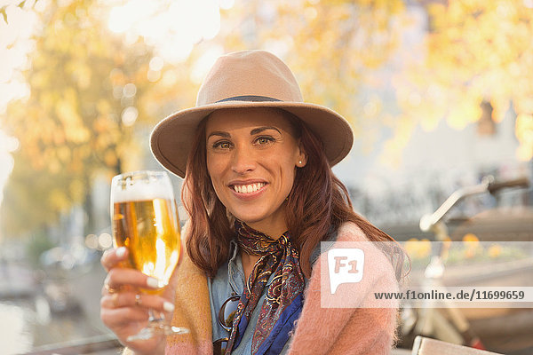 Portrait lächelnde junge Frau rösten Bierglas im Herbst Bürgersteig Cafe