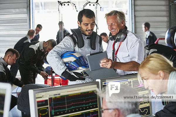 Manager und Formel-1-Fahrer mit digitalem Tablett in der Reparaturwerkstatt