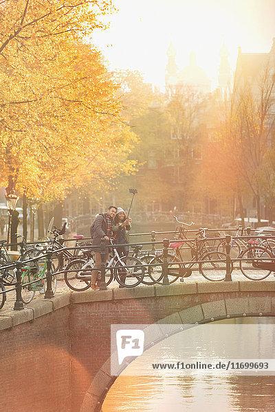 Junges Paar mit Fahrrädern nimmt Selfie mit Selfie-Stick auf Brücke über den Kanal in Amsterdam