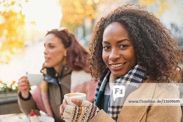 Portrait lächelnde junge Frau in warmer Kleidung trinkt Espresso im Straßencafé