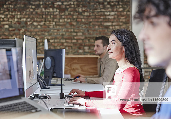 Mature woman working in office with young colleagues