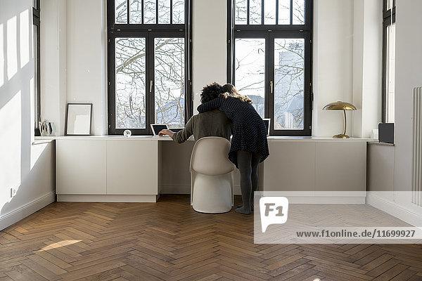 Pärchen arbeiten vor dem Panoramafenster zu Hause mit Laptop und Tablett