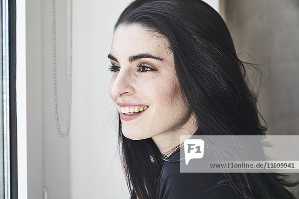 Lächelnde junge Frau schaut aus dem Fenster.