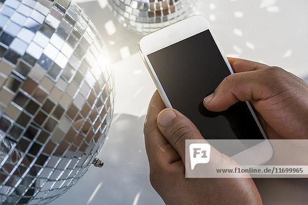 Nahaufnahme der männlichen Hände beim Tippen auf dem Smartphone