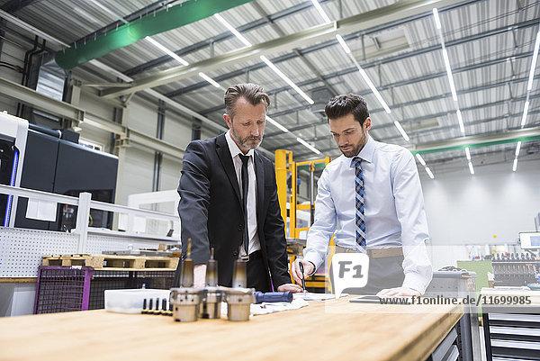 Zwei Geschäftsleute am Tisch in der Fabrikhalle bei der Produktprüfung