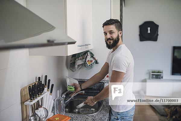 Junger Mann beim Geschirrspülen