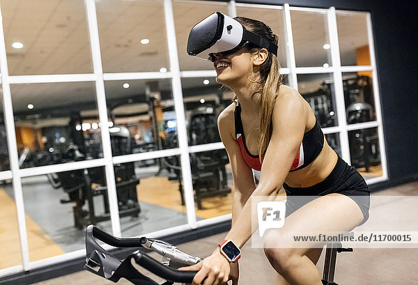 Woman with VR glasses on spinning bike in the gym