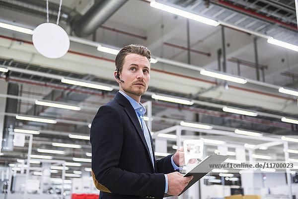 Mann mit Headset in der Fabrikhalle macht sich Notizen