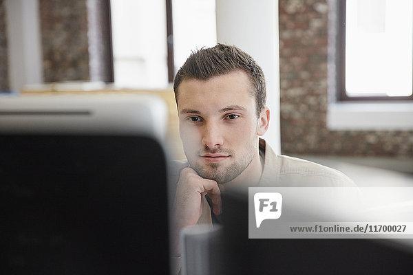 Junger Mann sitzt im Büro mit Computer