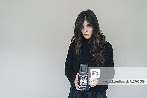 Dark-haired young woman holding vintage camera