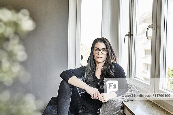 Bildnis einer jungen Frau mit Brille am Fenster