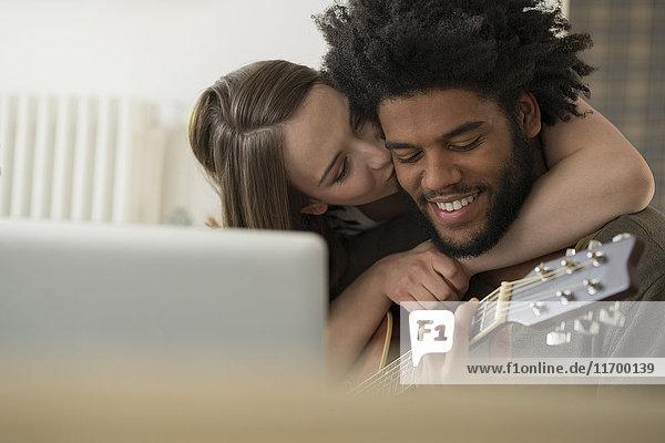Nahaufnahme einer Frau  die einen lächelnden Mann küsst  der vor dem Laptop Gitarre spielt.