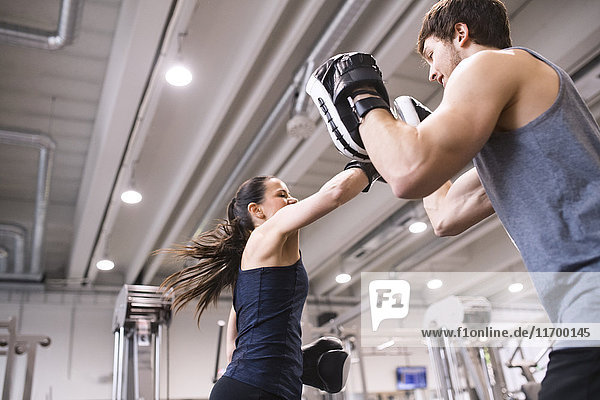Junge Frau beim Boxen mit ihrem Trainer