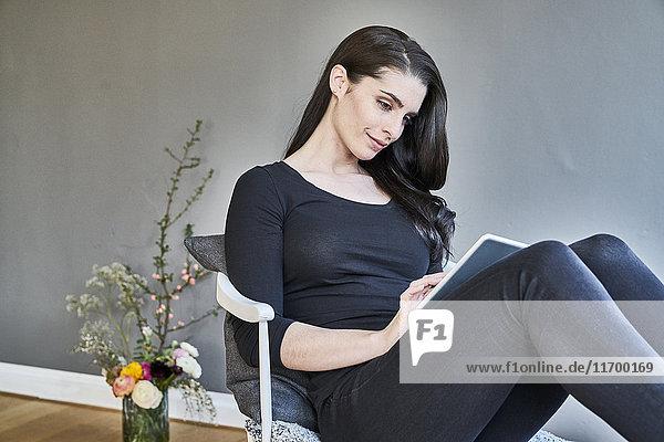 Lächelnde junge Frau mit Tablette zu Hause