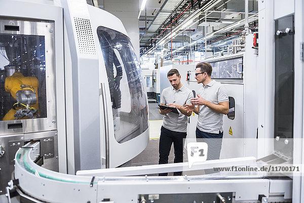 Zwei Männer reden an der Maschine in der Fabrikhalle.