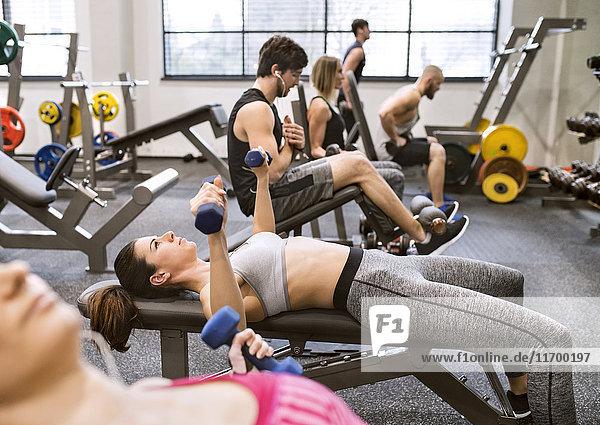 Junge Frau beim Training mit Hanteln im Fitnessstudio