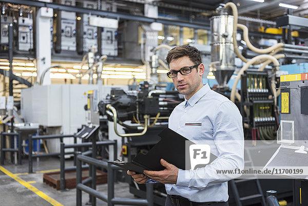 Porträt eines Mannes mit Dokumenten in der Fabrikhalle