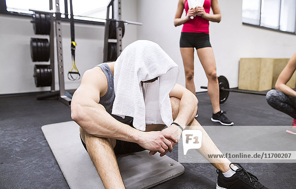 Exhausted athlete with towel on his head after exercising in gym