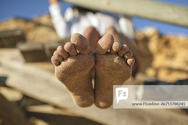 Sandige Füße der Frau am Strand