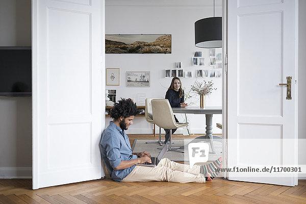 Mann zu Hause am Boden sitzend mit Laptop und Frau im Hintergrund