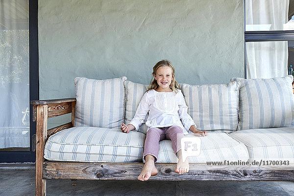Porträt eines lächelnden blonden Mädchens auf der Couch auf der Terrasse