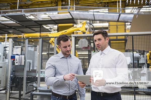Zwei Männer mit Tabletten reden in der Fabrikhalle