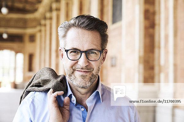 Porträt eines zufriedenen Geschäftsmannes mit Stoppelbrille