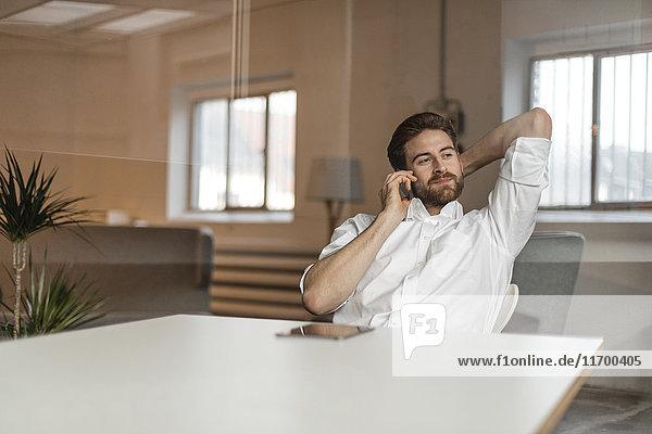 Porträt junger Freiberufler am Telefon im Loft