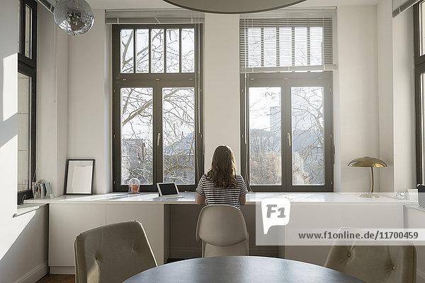 Frau vor dem Panoramafenster zu Hause mit Tablett