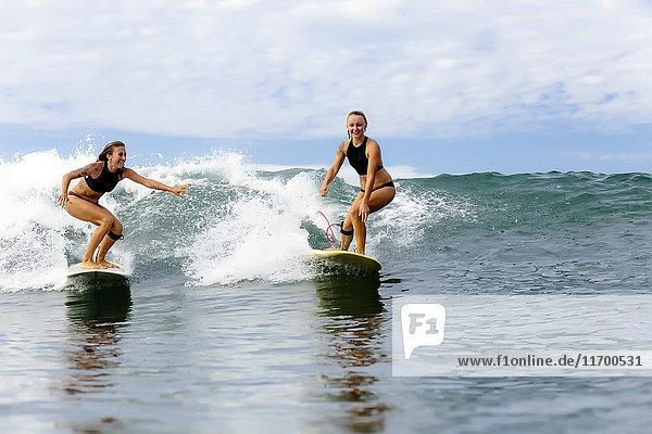 Zwei Mädchen beim Surfen im Meer