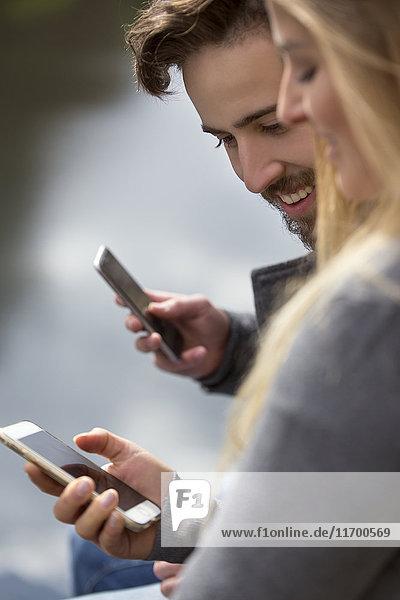 Junges Paar schaut aufs Handy