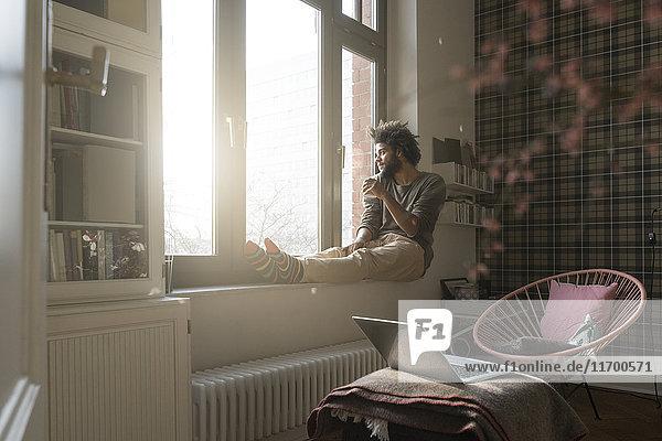 Mann sitzt auf der Fensterbank im Wohnzimmer und schaut nach draußen und hält eine Tasse.