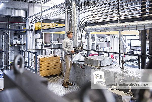 Mann mit Dokumenten,  der in die Fabrikhalle schaut.