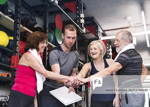 Gruppe von fitten Senioren mit Personal Trainer im Fitnessstudio