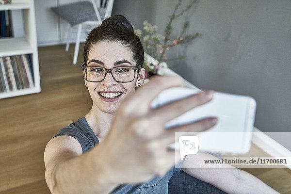 Lächelnde junge Frau nimmt einen Selfie mit nach Hause