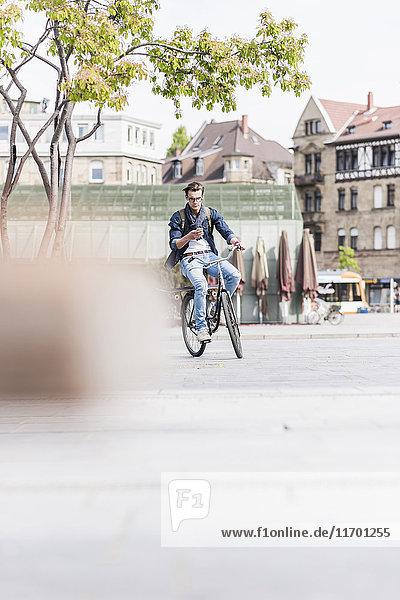 Junger Mann mit Fahrrad in der Stadt per Handy