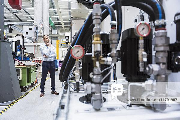 Mann in der Fabrikhalle mit Blick auf die Maschine