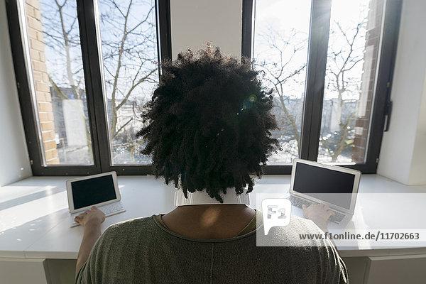 Mann arbeitet zu Hause vor dem Panoramafenster mit Laptop und Tablett