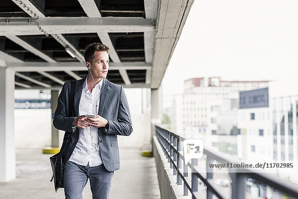 Junger Geschäftsmann mit Smartphone  zu Fuß auf Parkebene