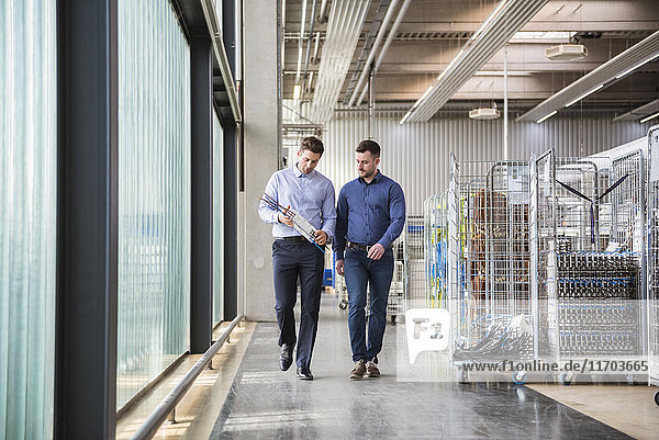 Zwei Männer  die in der Fabrikhalle herumlaufen und über das Produkt reden.