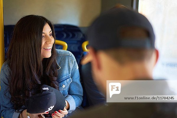 Exhilarated young Colombian woman laughing with friends while sitting in public transport in Malta  Europe