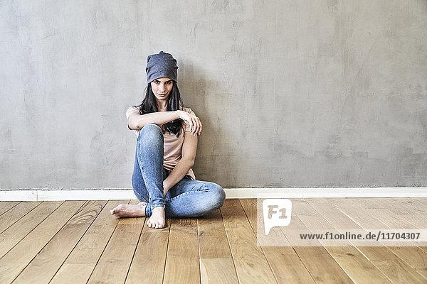 Junge Frau sitzt auf dem Boden in spärlichem Raum