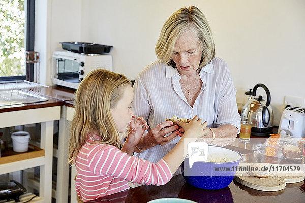 Großmutter und Enkelin bereiten das Essen in der Küche zu.