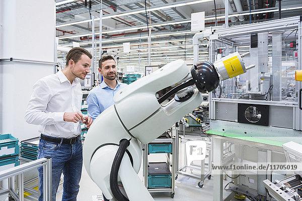 Zwei Männer betrachten den Montageroboter in der Fabrikhalle