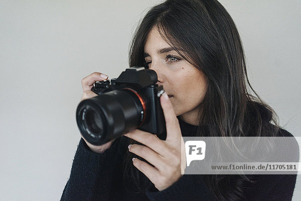 Dark-haired young woman holding a camera
