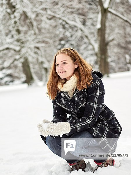Beautiful young girl wearing a winter coat and she have a snow ball in hand  Finnish winter day on February.