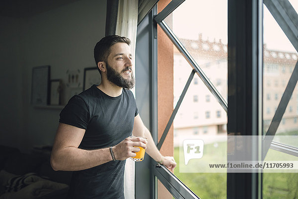 Young man drinking an orange juice at the window