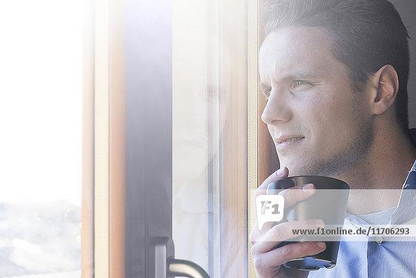 Geschäftsmann mit Tasse Kaffee aus dem Fenster schauend