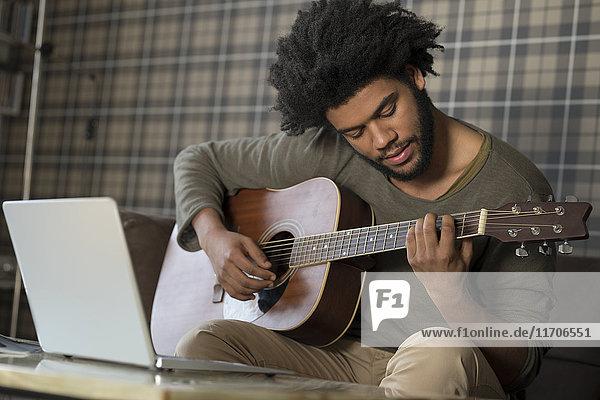 Mann sitzt im Wohnzimmer auf dem Sofa und spielt Gitarre vor dem Laptop.